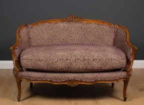 An 18th century French style walnut small sofa with purple spot upholstery and carved decoration