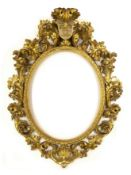 A 19th century Florentine carved giltwood frame of oval form with fleur-de-lis cresting and