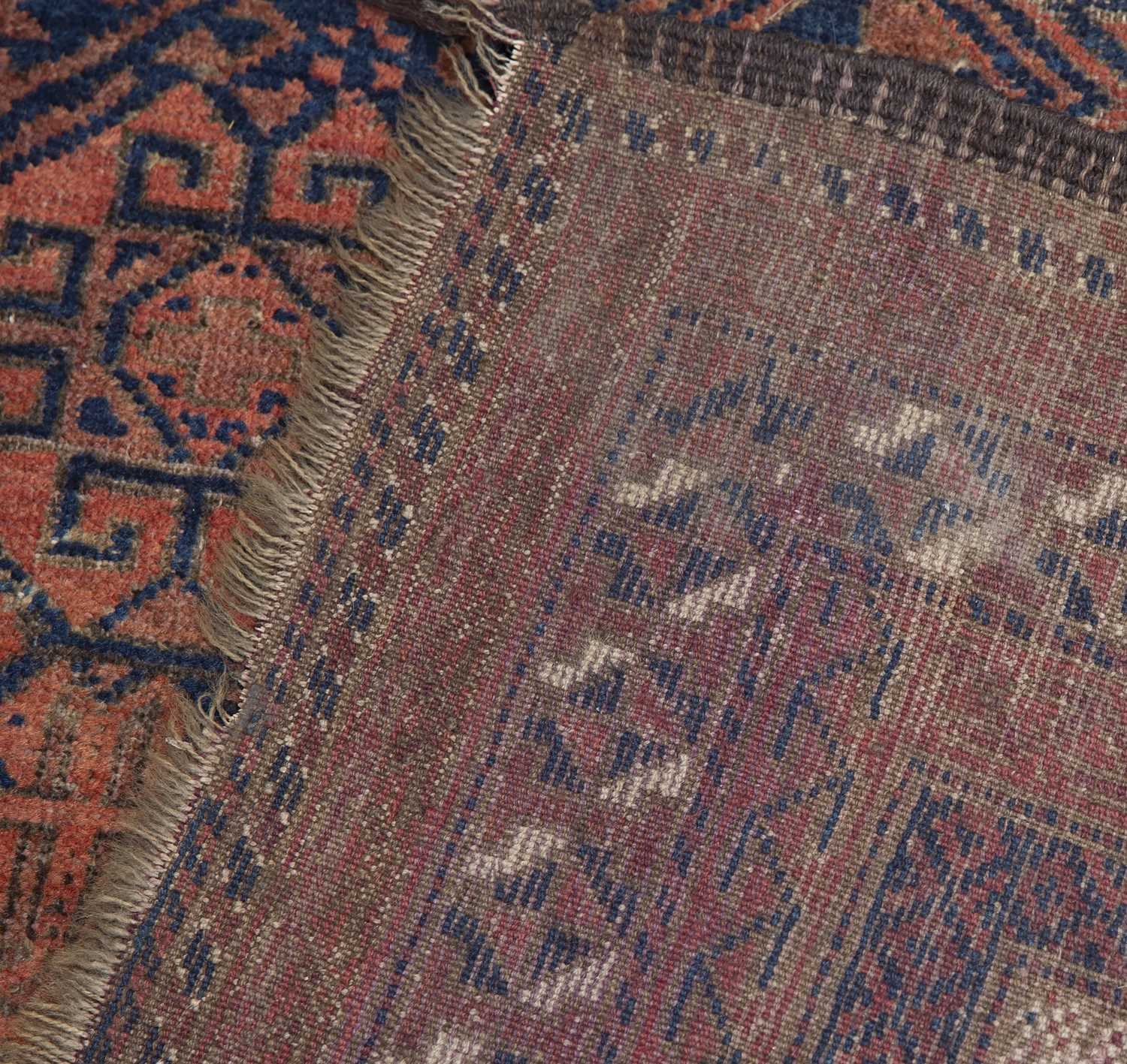 An old Belouch prayer rug with a central pattern of guls on a dark blue ground, 114 x 99cm and - Image 3 of 3
