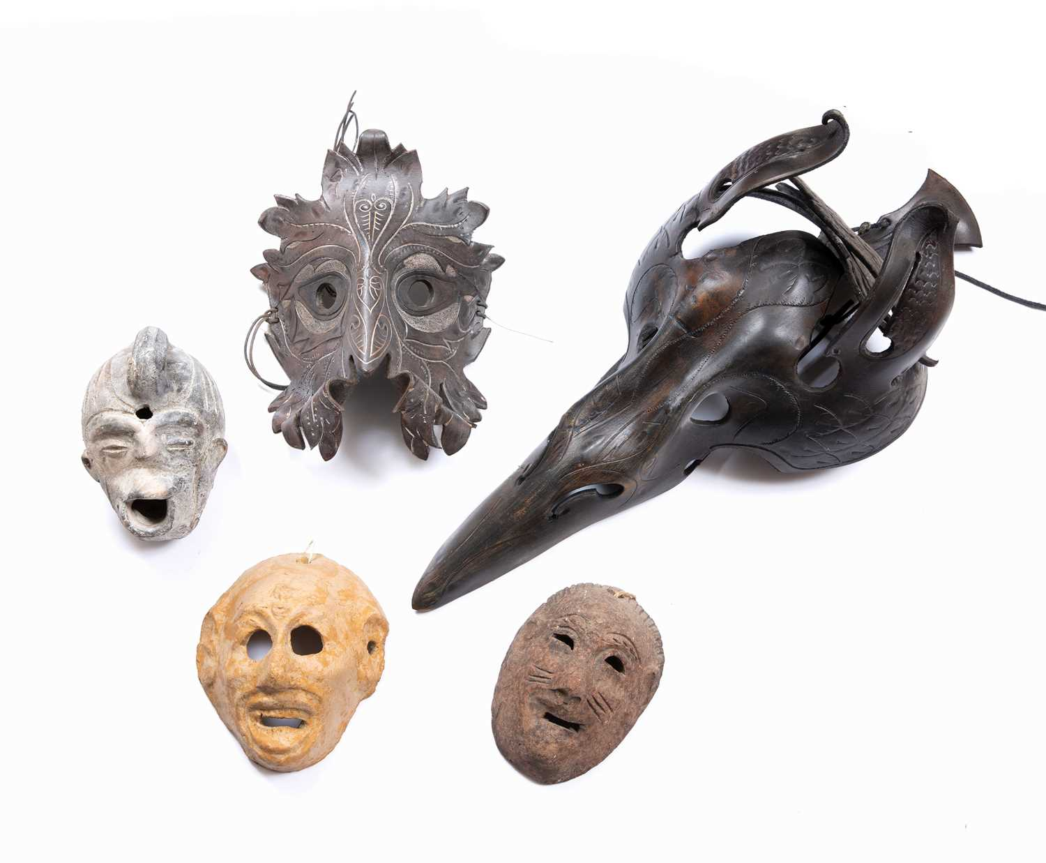 Capp, Justin - A leather 'Green Man' mask, another of horse like creature form, two pottery face