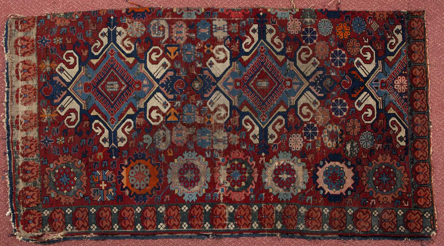 An antique Caucasian Seychor rug fragment with scrolled medallions on a red ground, 156 x 85cm