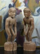 A pair of carved wooden Bullul rice divinity figures, male and female, each stooped and on a