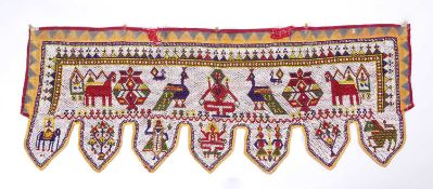 An Indian beadwork doorway hanging decorated with stylised polychrome animals, 125 x 45cm