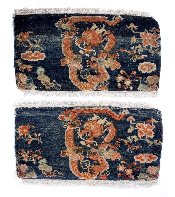 A pair of Tibetan dark blue ground mats with symbolic dragon decoration, 66 x 34cm and 67 x 36cm (