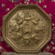 A Northern Indian octagonal brass wall plaque decorated with deities, 49cm wide