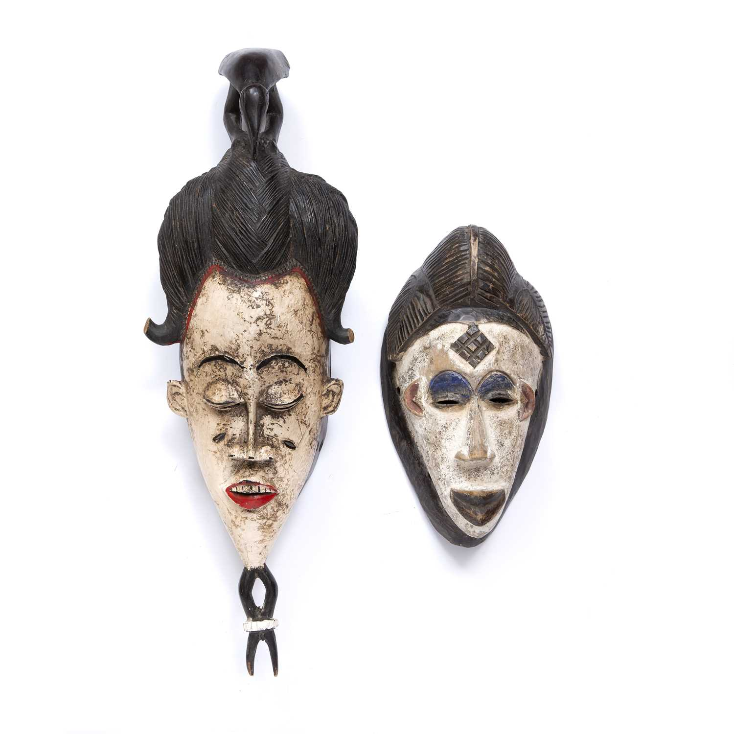 A Baule mask, Ivory Coast, carved wood with high incised coiffure topped by a bird with white and