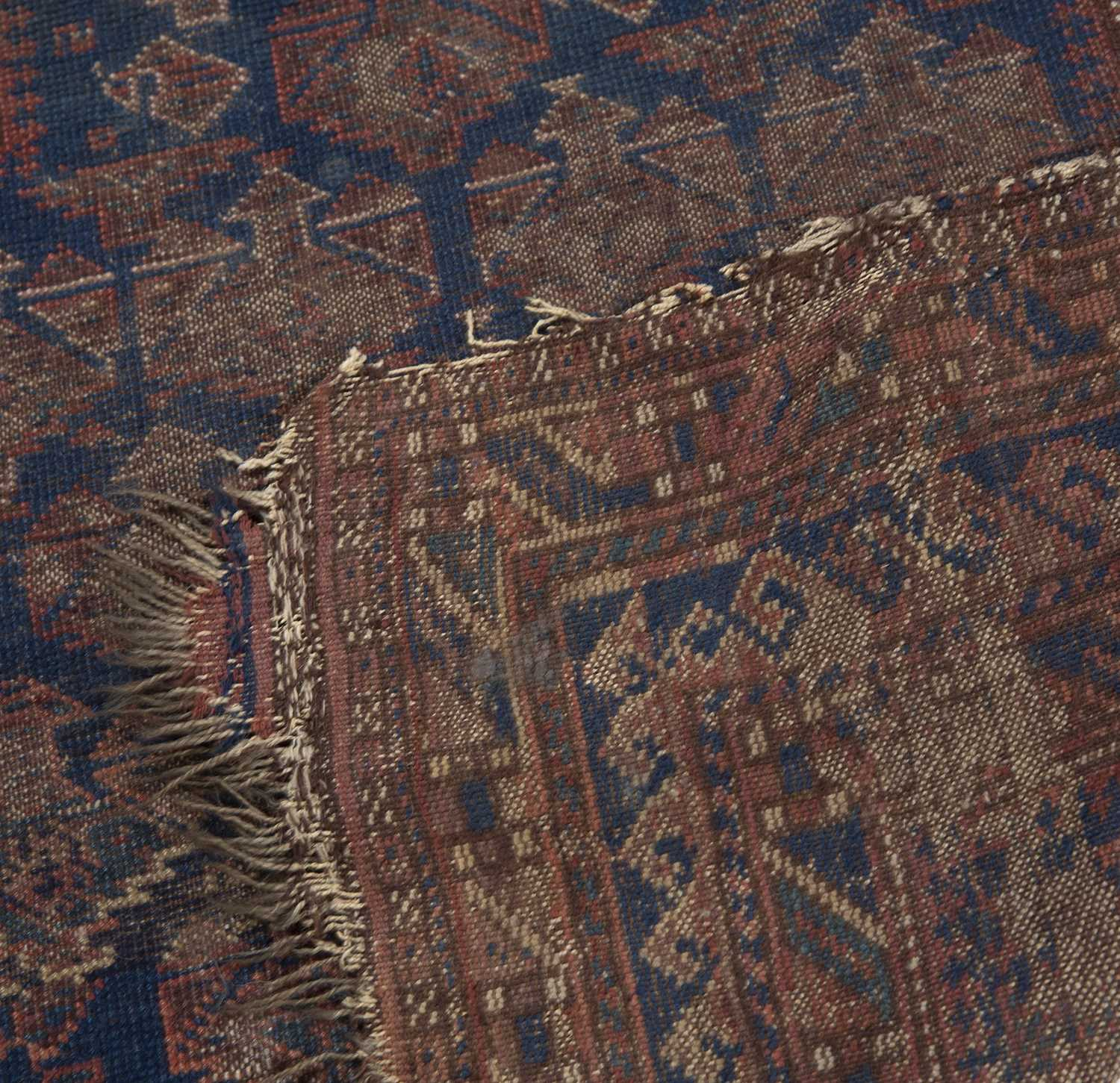 An old Belouch prayer rug with a central pattern of guls on a dark blue ground, 114 x 99cm and - Image 2 of 3