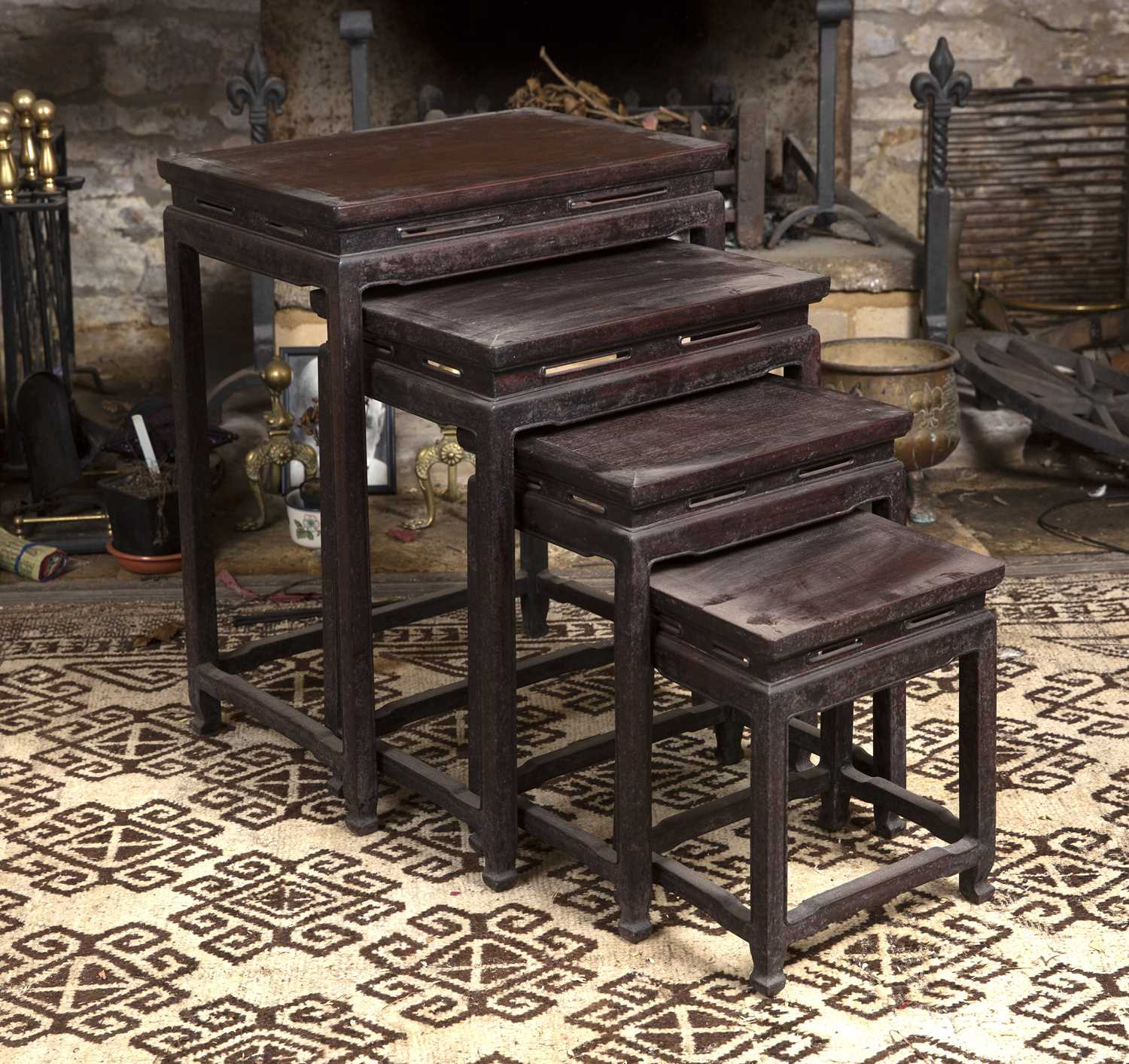 A nest of four graduated Chinese hardwood occasional tables, with pierced friezes, on square legs,
