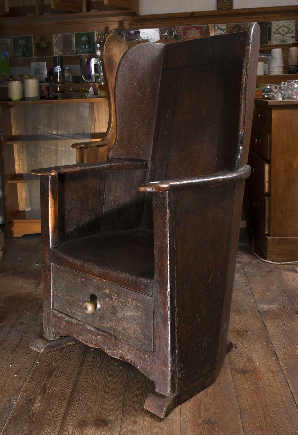 An 18th century oak and stained pine lambing chair, with wing back, curved arms and solid seat, - Image 2 of 3