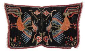 A Tibetan dark blue ground child's saddle rug with polychrome twin phoenix motifs, 115 x 62cm