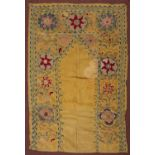 Part of an Uzbek Susani with a colourful star and scrolling design on a yellow ground, 142 x 90cm