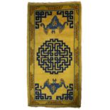 A Chinese mustard yellow ground rug decorated blue twin bats with central symbolic medallion, 180