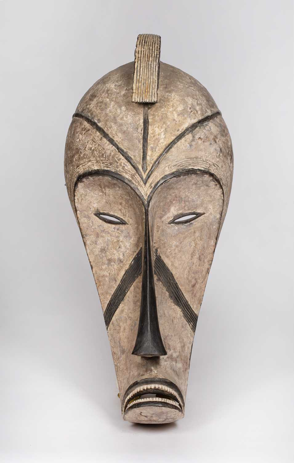 A Fang mask, Gabon, carved wood with incised line marks with black and white pigments, 74cm high