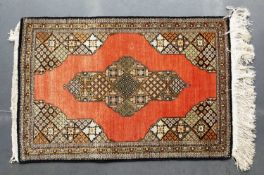 A Persian silk Qum mat with central star shaped medallion on a brick red ground, 84 x 57cm