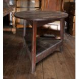 A 19th century oak cricket table, the circular top on three slightly splayed legs, with triangular