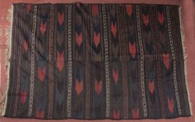 An old Belouch flat weave carpet decorated an arrow motif with bands of stars on a dark red