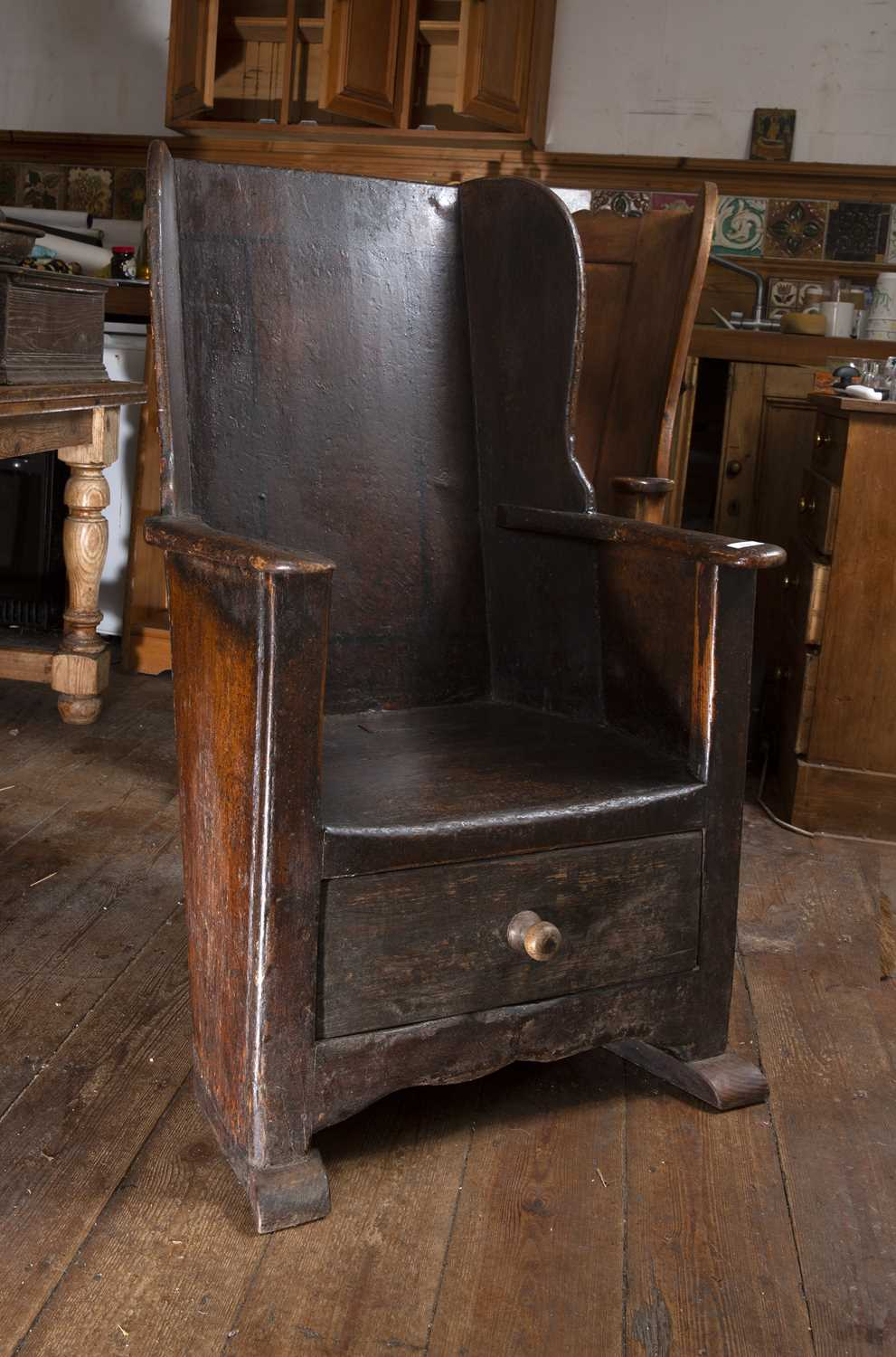 An 18th century oak and stained pine lambing chair, with wing back, curved arms and solid seat,