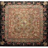 A 19th century Persian needlework table cover with an intricate scrolling design within a black