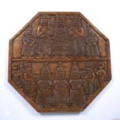 A Benin carved wooden hexagonal table top with OBA figures and multiple attendants, 61cm