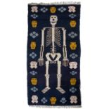 A Chinese blue ground rug with a central design of a skeleton with mask surround, 188 x 100cm