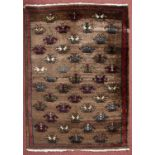 A Turkish rug with multi-coloured flower design on a brown ground, 115 x 81cm