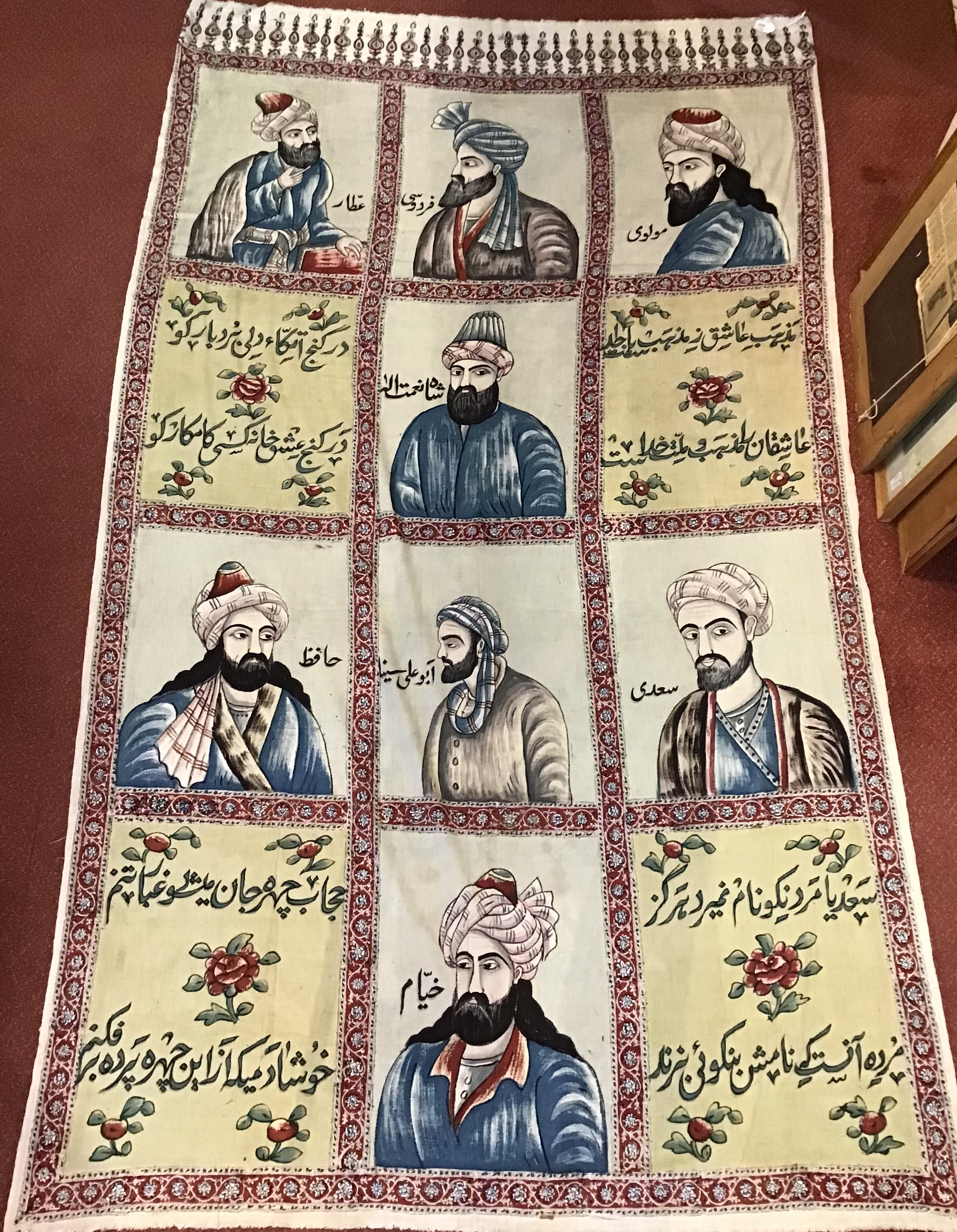 An Isfahan polychrome printed wall hanging depicting eight portraits with inscriptions, 230 x 133cm