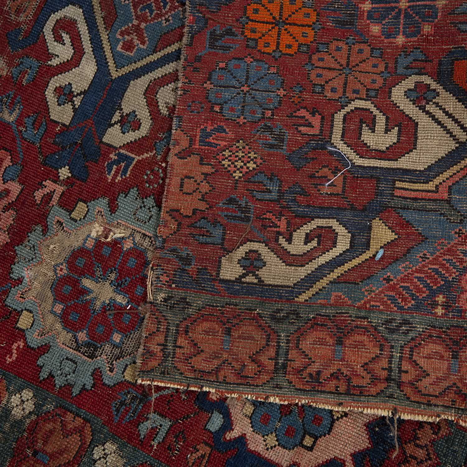 An antique Caucasian Seychor rug fragment with scrolled medallions on a red ground, 156 x 85cm - Image 2 of 2