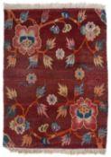 A Tibetan dark rust red ground saddle rug or mat decorated polychrome flower heads, 76 x 58cm