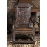 A late 18th century oak wainscot chair, the shaped panelled back carved with a stylised flowerhead