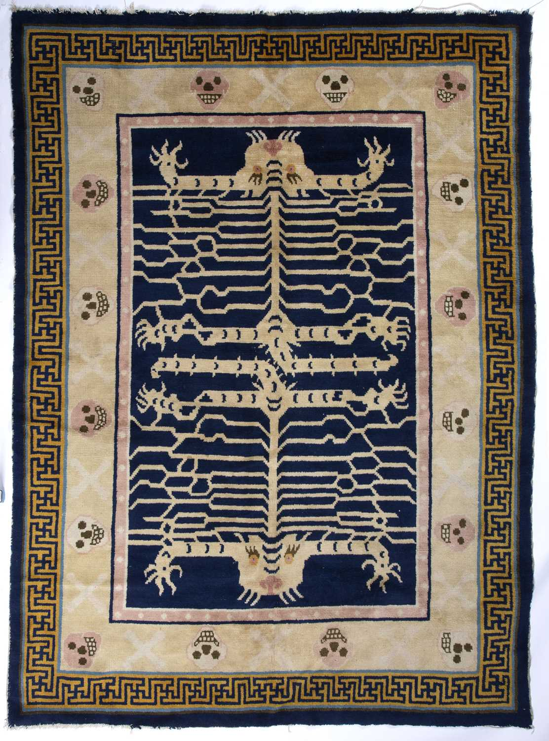 A Chinese blue and white ground rug decorated with two stylised tigers with mask surround and a
