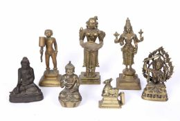A group of seven Indian and Chinese brass deity figures including Buddha, Shiva, 21.8cm high (7)