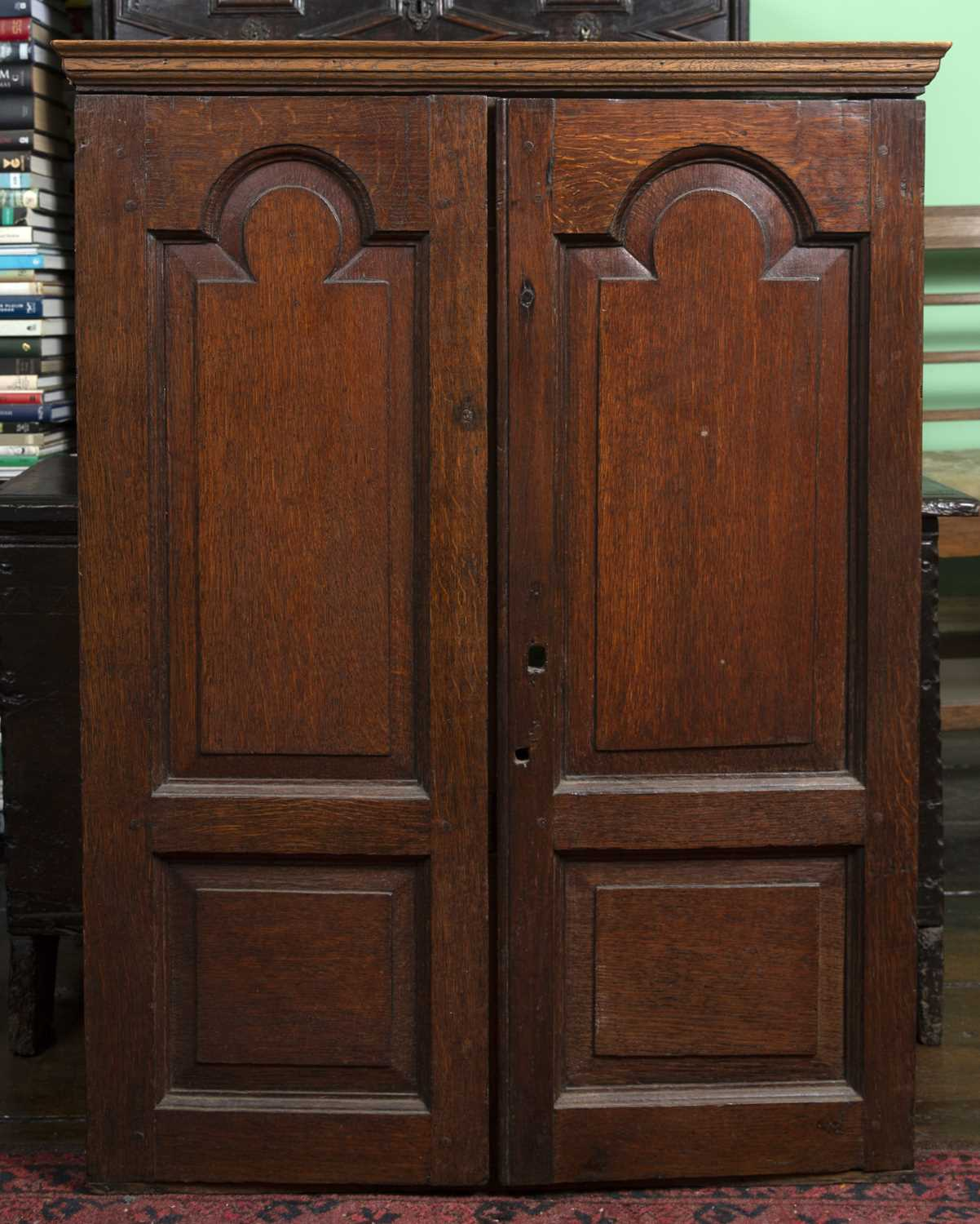 An 18th century oak small cupboard, having a pair of arch panelled doors enclosing shelves and