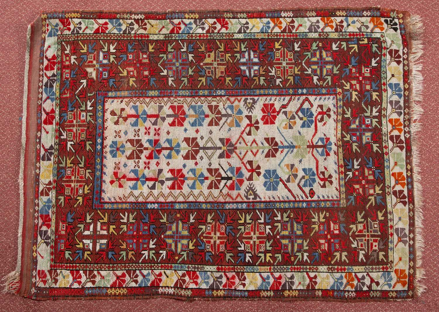 A Turkish Milas rug with a multi-coloured complex geometric design on a red and white ground, 120