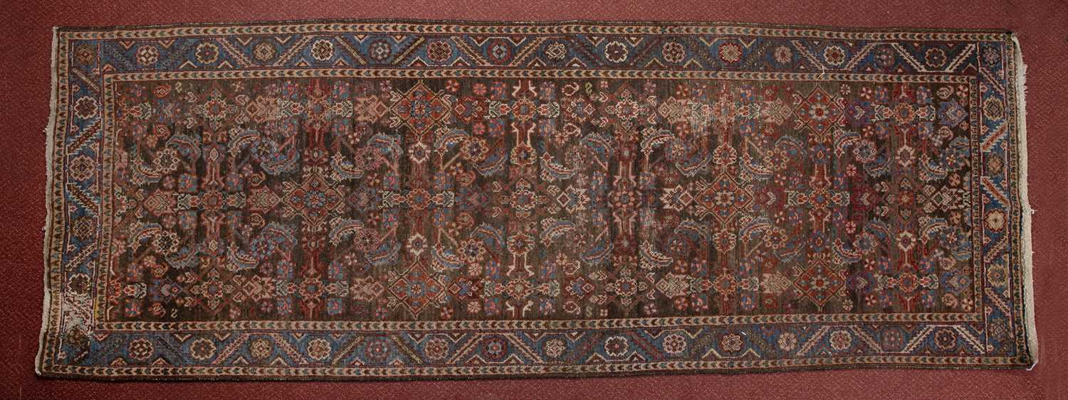 A Persian Bakshaish runner with a complex design of flowers and motifs within a triple border, 302 x