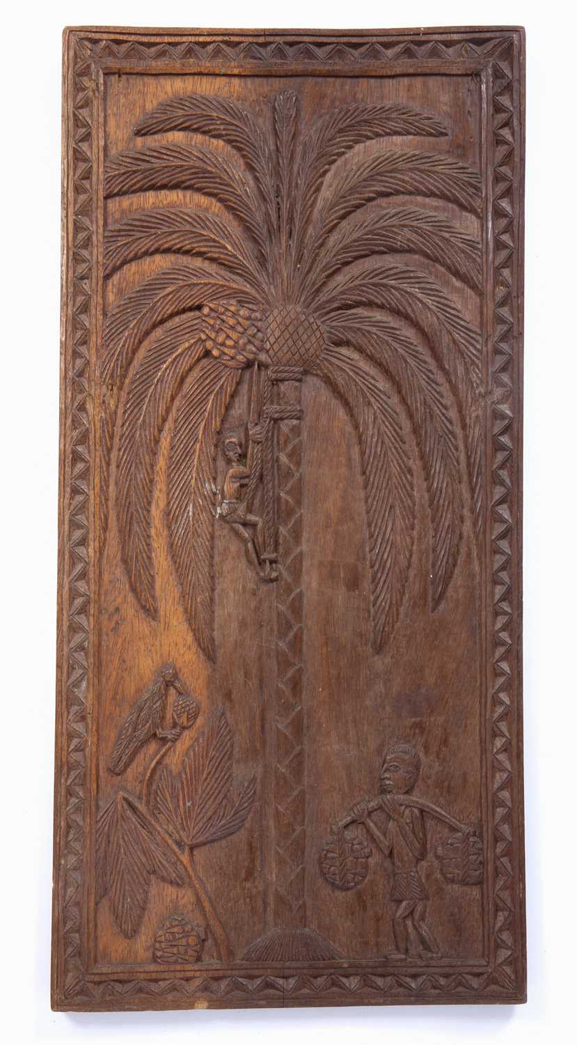 A Benin carved wooden rectangular panel depicting a man climbing a palm tree, dotted inscription