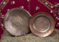 A Persian copper on tin shallow circular dish decorated with three figures, 21cm diameter and an