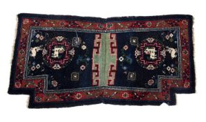 An Antique Tibetan dark blue ground saddle rug decorated Fo dogs and with central hooked green panel