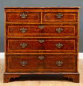 An 18th century walnut chest of two short and three long drawers with later brass handles and raised