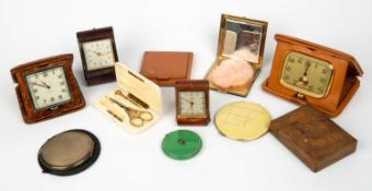 A black enamelled ladies compact, a silver compact, two further compacts, a Longines desk timepiece,