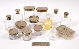 A collection of silver topped cut glass bottles and boxes all with engine turned decoration together