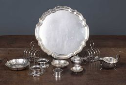 A pair of silver toast racks and further silver consisting of a sauceboat, strawberry dish, napkin