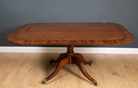 A 19th century mahogany tilt top dining table with a turned stem, four splay legs with brass paw