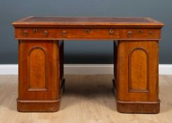 A Victorian mahogany pedestal desk with a brown leatherette inset top, nine drawers with covered