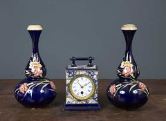 An antique pottery timepiece 19cm high together with a pair of flower decorated blue ground vases of