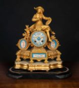 A French gilt mantle clock set with porcelain panels, the case decorated by a seated artist, the