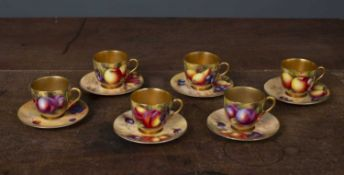 A set of six Royal Worcester porcelain cups and saucers each gilded and having hand painted fruit