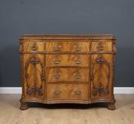 A George III style serpentine fronted sideboard with four central drawers flanked by two drawers and