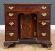A George III mahogany kneehole desk with one long drawer and six short drawers, a central recessed