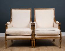 A pair of oak framed armchairs with cream upholstery and turned legs, 66cm wide x 58cm deep x 44cm