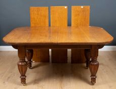 An oak extending dining table with three leaves, turned and carved legs and brass casters, 160cm